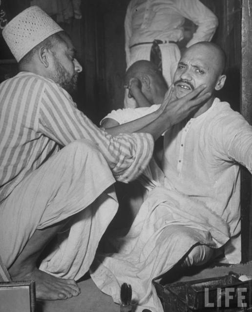 Barber+appraising+growth+on+man%2527s+face+before+giving+him+a+shave+in+market+place+-+Lahore+1946