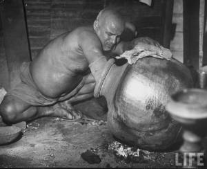 Man+stirring+food+in+large+pot+which+has+been+heating+over+coals+-+Lahore+1946