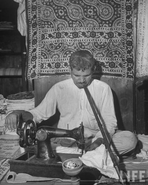 Man+using+a+hand-cranked+sewing+machine+to+make+clothes+as+he+smokes+a+hooka+pipe+in+his+shop+-+Lahore+1946