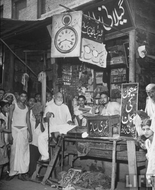 Shopkeepers+posing+with+others+at+their+spice+store+stall+in+market+area+of+the+city+-+Lahore+1946