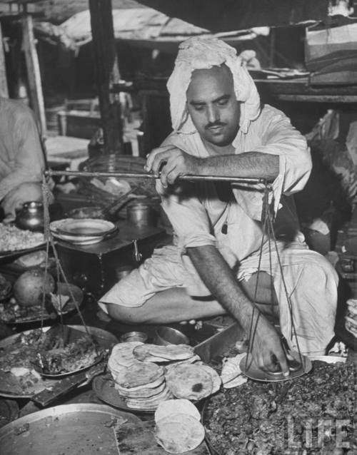 Shopkeeper+using+balance+scale+to+weigh+portion+of+food+for+a+customer+in+his+food+stall+at+market+-+Lahore+1946
