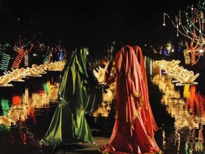 Models of women look over a sea of illuminated lillies in the Lahore canal for the Jashan-e-Baharan celebrations
