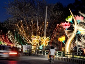 Motorist ride past colorful light and models set up for the Jashan-e-Baharan celebrations