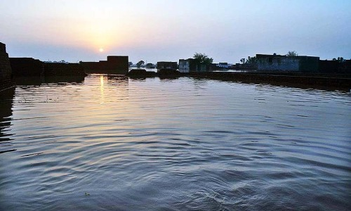 A view of houses surrounded by flood water in Rana Town area of Lahore.— Photo by APP